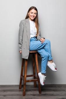 白い壁に椅子に座っているシャツとジーンズのかなり若い幸せな笑顔の女性の縦の肖像画