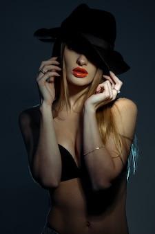 Вертикальный портрет стройной молодой женщины в черном бюстгальтере с красными губами в шляпе с широкими полями позирует