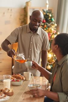 Вертикальный портрет улыбающегося афроамериканца, разливающего чай для жены, наслаждаясь рождественским ужином дома