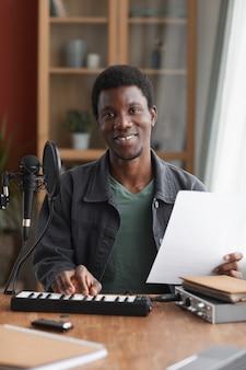홈 스튜디오에서 음악을 녹음하는 동안 마이크에 노래 웃는 아프리카 계 미국인 남자의 세로 초상화