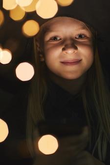Вертикальный портрет улыбающейся девочки-подростка и во время вечеринки на хэллоуин на открытом воздухе в темноте, копией пространства