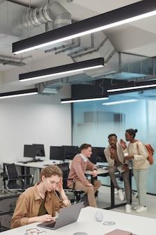 Вертикальный портрет подчеркнутой молодой женщины, использующей ноутбук в офисе или коворкинге с группой людей в фоновом режиме, копией пространства