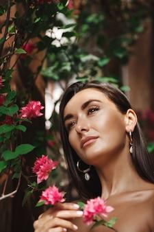 熱帯の花々の近くに立って、夢のように見つめている日焼けした白人女性の縦の肖像画。