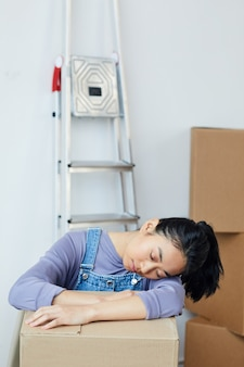 Вертикальный портрет усталой азиатской женщины, спящей на картонной коробке во время упаковки для переезда или переезда в новый дом