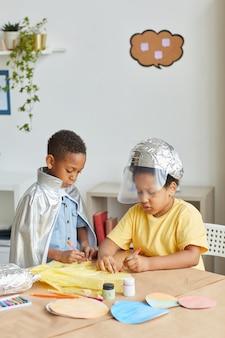 Вертикальный портрет двух афроамериканских мальчиков, играющих в космонавтов и шящих скафандры во время урока искусства и ремесел в дошкольном учреждении или центре развития