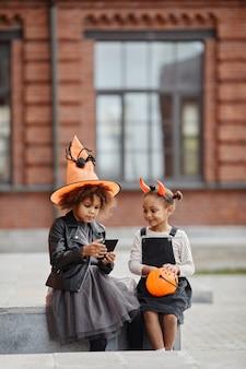 屋外でハロウィーンの衣装を着て、smartphを使用している2人のアフリカ系アメリカ人の女の子の垂直の肖像画...