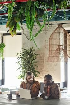 Вертикальный портрет двух современных мужчин, сотрудничающих над проектом во время деловой встречи в зеленом офисе или интерьере кафе, копирование пространства