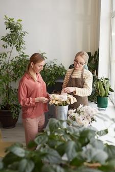 花屋スタジオ、コピースペースで仕事を楽しみながら花束を配置する2人の若い女性の縦の肖像画
