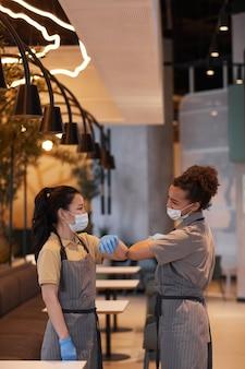 카페에서 일하는 동안 비접촉 인사로 팔꿈치를 부딪치는 두 젊은 여성의 세로 초상화, 코비드 안전 개념