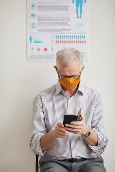 Вертикальный портрет седого пожилого мужчины в маске и использующего смартфон во время ожидания в очереди в медицинской клинике