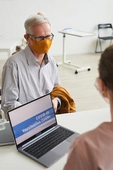의료 센터에서 코비드 백신을 등록하는 동안 마스크를 쓴 백인 머리 노인의 세로 초상화, 복사 공간