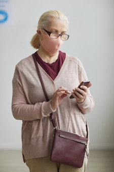 Вертикальный портрет седой пожилой женщины в маске и использующей смартфон, стоя на белом фоне в клинике