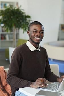 バックグラウンドで人々と大学図書館でラップトップを使用しながらカメラに笑みを浮かべて若いアフリカ系アメリカ人男性の縦の肖像画
