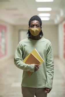 학교 복도에서 마스크를 쓰고 카메라를 바라보는 젊은 아프리카계 미국인 남자의 세로 초상화