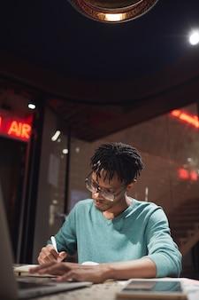 집에서 늦게 또는 어두운 사무실에서 일하는 젊은 아프리카 계 미국인 남자의 세로 초상화