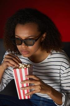 家でテレビを見て、暗い部屋に座ってポップコーンを食べる若いアフリカ系アメリカ人女性の縦の肖像画