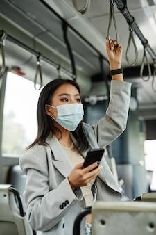 Вертикальный портрет молодой азиатской женщины в маске в автобусе и использующей смартфон во время поездок по городу