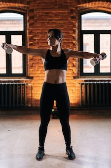 引き込まれた腕にダンベルを保持しているアクティブウェアを身に着けている美しい強い体を持つ若い運動女性の垂直方向の肖像画。暗いジムで運動する白人フィットネス女性のトレーニング。