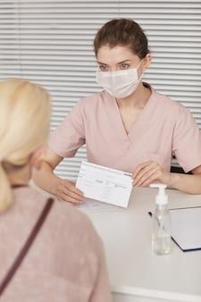 Вертикальный портрет молодой медсестры в маске при регистрации пациентов для вакцинации против covid в медицинском центре