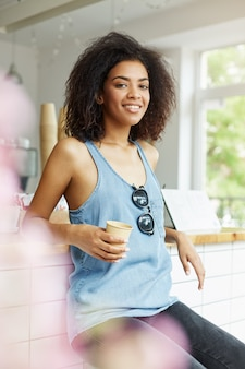 Вертикальный портрет молодой красивой жизнерадостной темнокожей африканской студентки с волнистыми волосами в синей рубашке, сидящей в кафе, пьющей латте, улыбающейся, смотрящей в камеру со счастливым и относительным