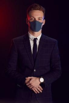 フェイスマスクを着用し、黒い背景に立ってパーティーでポーズをとっている間カメラを見ている若い男の縦の肖像画