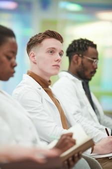 연구실 가운을 입은 젊은 남자의 세로 초상화는 청중석에 나란히 앉아 대학에서 의학 강의를 듣는 동안