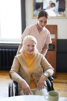 Вертикальный портрет молодой женщины, помогающей улыбающейся пожилой женщине в инвалидной коляске в доме престарелых