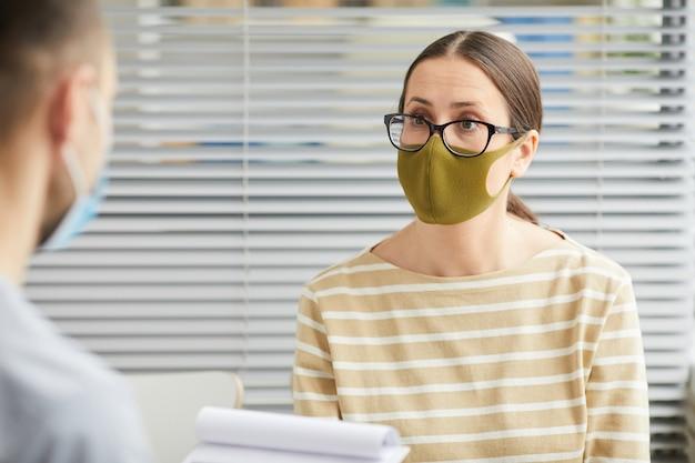 Вертикальный портрет молодой женщины в маске и слушания врача во время ожидания в очереди в медицинской клинике
