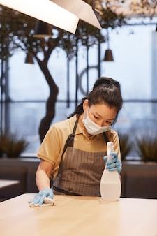 モダンなレストランのインテリア、covid安全コンセプトのテーブルを掃除しながらマスクを身に着けている若い女性の縦の肖像画