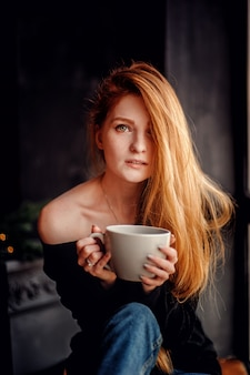 Vertical portrait of one adult young woman with red hair in black sweater holding big cup of drink looking at camera enjoying good morning inside house with blurred dark grey background