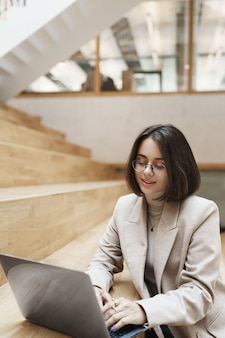 Vertical portrait of professional, successful young short-haired woman in beige jacket, typing message to client using laptop, working on remote, online project, studying or freelancing.