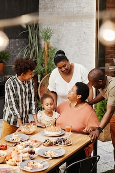 Vertical portrait of senior africanamerican woman celebrating birthday with family and blowing candl...