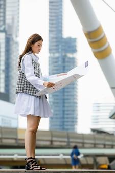 Вертикальный портретный снимок милой улыбающейся молодой взрослой азиатской женщины в элегантной повседневной модной одежде, стоящей, держащей бумажную карту города и смотрящей в камеру на размытом фоне высокого здания