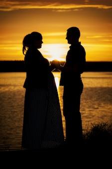 黄色の夕日のビーチで彼の妊娠中の妻と男の縦の肖像画のシルエット