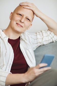 Vertical portrait of smiling bald woman rubbing head and looking away pensively while sitting in cozy armchair at home, alopecia and cancer awareness