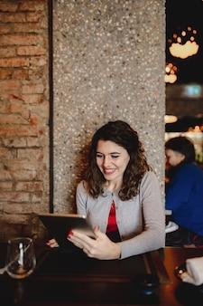 Вертикальный портрет усмехаясь кавказской молодой женщины в ресторане держа таблетку.