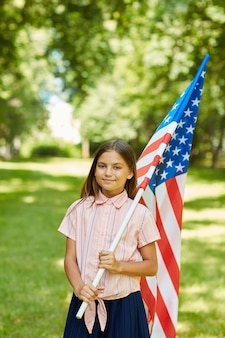 Vertical portrait of smiling schoolgirl carrying american flag while standing outdoors in sunlight