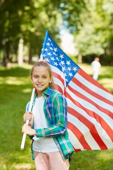 Vertical portrait of smiling teenage girl carrying american flag while standing outdoors in sunlight