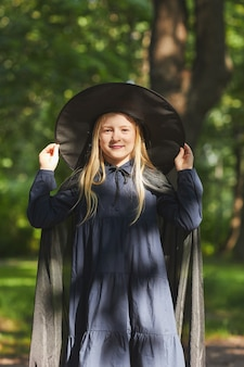 Vertical portrait of smiling teenage girl dressed as witch for halloween  while standing outdoors in sunlight