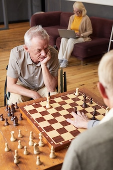 Vertical portrait of two senior men playing chess and enjoying activities in cozy nursing home