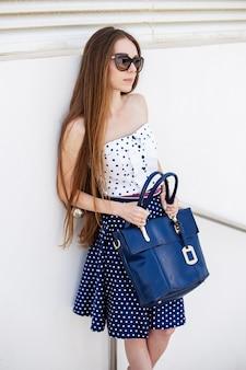 Ritratto verticale di una donna che tiene una borsa e indossa occhiali da sole
