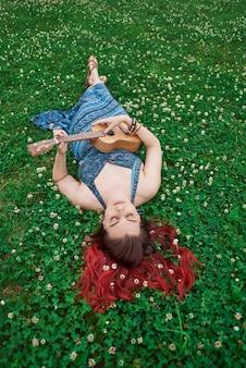세로 세로 여자는 눈을 감고 우쿨렐레를 연주하는 여름에 잔디에 누워 이완합니다.