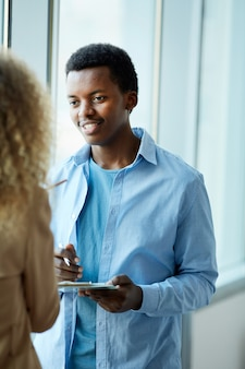Vertical portrait of young african-american man talking to female friend while standing by window in college or office