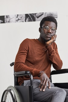 Vertical portrait of young african-american man using wheelchair and  while posing pensively against white wall in modern art gallery