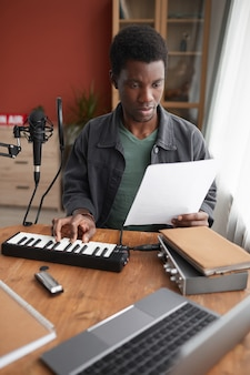 Vertical portrait of young african-american musician composing music in home recording studio