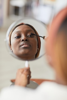 Vertical portrait of young african-american woman doing makeup, focus on mirror reflection, copy space Premium Photo