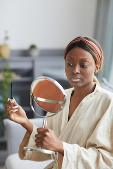 Vertical portrait of young african-american woman doing makeup at home in morning