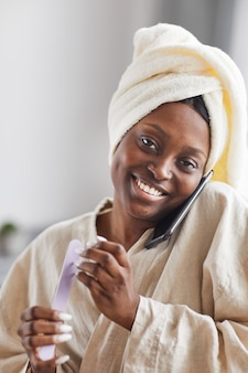 Vertical portrait of young african-american woman enjoying beauty routine at home and speaking by smartphone