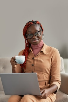 Vertical portrait of young african-american woman holding coffee mug and laptop while enjoying work from home office