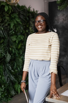 Vertical portrait of young african-american woman smiling at camera while standing in modern office interior decorated by plants